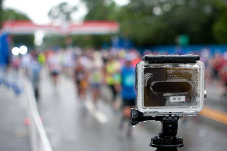 documenting: Atlanta, GA, USA - July 4, 2015:  A GoPro camera mounted on a tripod shoots time-lapse photography of runners crossing the finish line in the rain at the annual Peachtree Road Race 10K in Atlanta. Editorial
