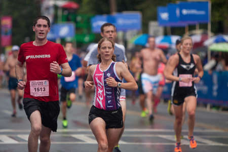 striving: Atlanta, GA, USA - July 4, 2015:  Tired runners push for the finish line in the rain, at the 46th running of the Peachtree Road Race 10K in Atlanta.
