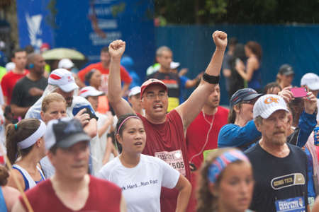 Atlanta, GA, USA - July 4, 2015:  A man raises his arms triumphantly among a crowd of runners crossing the finish line in the rain at the annual Peachtree Road Race 10K in Atlanta.