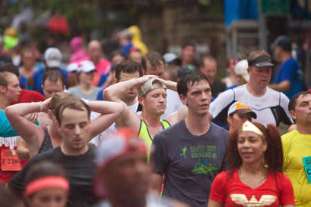 fulfilling: Atlanta, GA, USA - July 4, 2015:  Runners put their hands on their heads to catch their breath after crossing the finish line in the rain at the 46th running of the Peachtree Road Race in Atlanta. Editorial