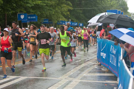 adrenaline rush: Atlanta, GA, USA - July 4, 2015:  Exhausted runners approach the finish line in the rain at the 46th running of the Peachtree Road Race 10K in Atlanta.