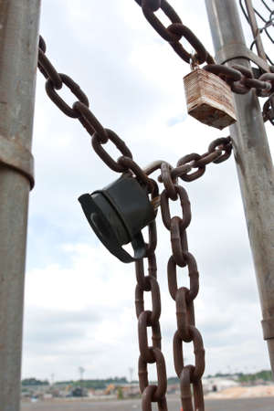 Padlocks and chains secure gate to industria work area