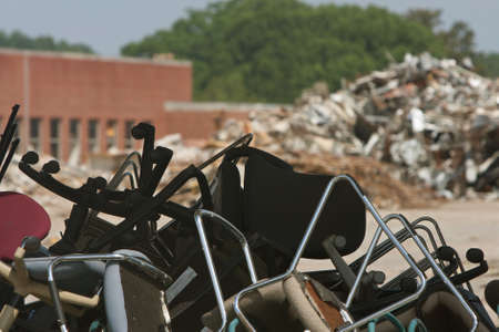 trashed: Discarded office chairs and debris piled up at demolition site. Stock Photo