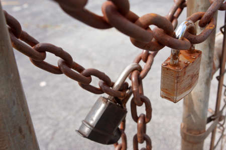 secure site: Padlocks And Rusted Chains Secure Gate At Industrial Site