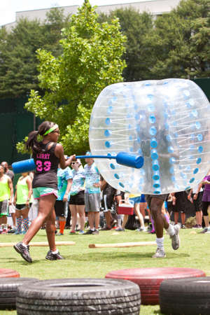 outrageous: Atlanta, GA, USA - July 11, 2015:  A man wearing a plastic bubble gets hit while running the bubble gauntlet at Atlanta Field Day in the Old Fourth Ward Park in Atlanta.