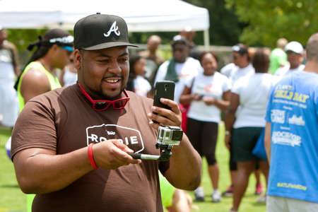 documenting: Atlanta, GA, USA - July 11, 2015:  A man operates a GoPro camera on a selfie stick by using his smart phone, at the Atlanta Field Day in the Old Fourth Ward Park in Atlanta.
