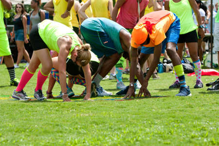 Atlanta, GA, USA - July 11, 2015:  Young adults bend and stretch playing grass twister at Atlanta Field Day, an event where adults compete in kids games, in the Old Fourth Ward Park in Atlanta, GA.