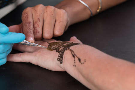 skillfully: Atlanta, GA, USA - September 12, 2015:  An artist skillfully designs a henna temporary tattoo on a womans hand at the 5 Arts Fest in Atlanta.