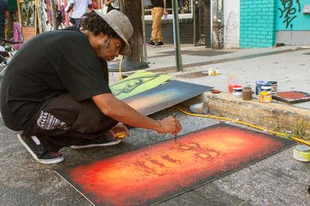 flicking: Atlanta, GA, USA - September 12, 2015:  An artist flicks yellow paint onto the painting hes creating at the 5 Arts Fest in Atlanta.