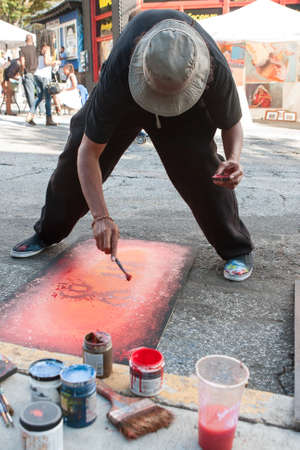 flicking: Atlanta, GA, USA - September 12, 2015:  An artist flicks red paint onto the painting hes creating on the pavement at the 5 Arts Fest in Atlanta.