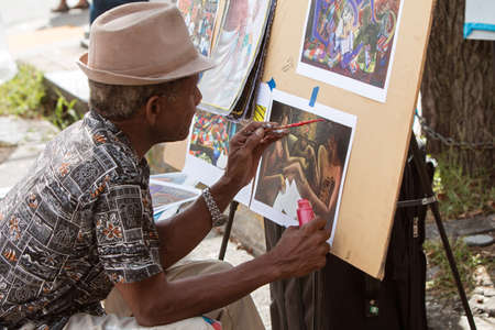 skillfully: Atlanta, GA, USA - September 12, 2015:  An artist skillfully paints a scene on a piece of paper at the 5 Arts Fest in Atlanta.