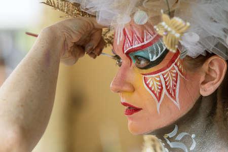 body paint: Atlanta, GA, EE.UU. - 12 de septiembre de 2015: Un artista con habilidad se aplica la pintura de carrocer�a de color a la cara de un modelo femenino en el ecl�ctico 5 Artes Fest en Atlanta. Editorial