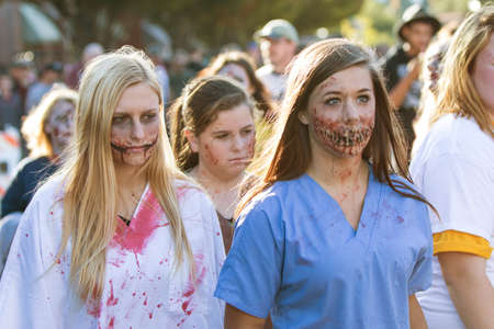 ghoulish: Canton, GA, USA - October 17, 2015:  Teenage girls in bloody zombie makeup and nurses scrubs walk among the crowd at the Cherokee Zombie Fest.