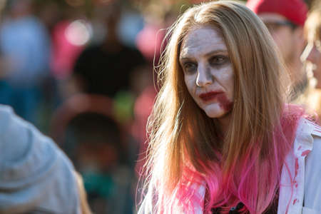 ghoulish: Canton, GA, USA - October 17, 2015:  A woman wearing zombie makeup wanders through the crowd at the Cherokee Zombie Fest in Canton, GA.