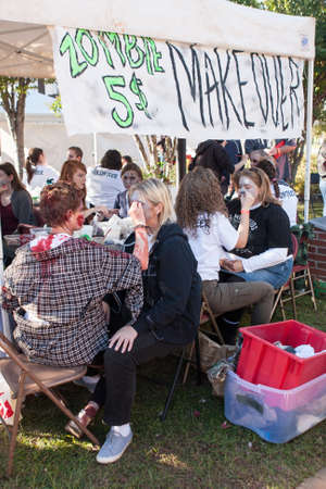 cherokee: Canton, GA, USA - October 17, 2015:  Makeup artists give festival goers zombie makeovers for 5 at the Cherokee Zombie Fest in Canton, GA.