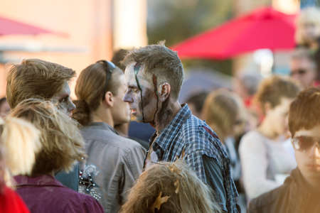 repugnant: Canton, GA, USA - October 17, 2015:  A man dressed as a ragged, bloody zombie wanders among the crowd at the Cherokee Zombie Fest in Canton, GA. Editorial