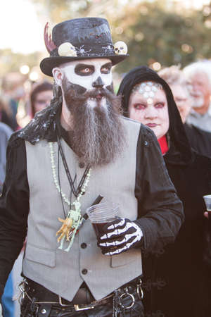 ghoulish: Canton, GA, USA - October 17, 2015:  A man in a voodoo costume walks among the crowd at the Cherokee Zombie Fest in Canton, GA.