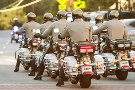 unison: Canton, GA, USA - October 17, 2015:  A group of local motorcycle police officers in the Sheriffs Department ride through town in unison as part of the Cherokee Zombie Fest in Canton, GA.