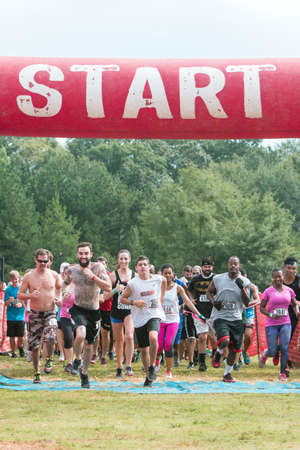Conyers, GA, USA - August 22, 2015:  A pack of runners takes off from the start line in one of the many waves of competitors participating in the Rugged Maniac obstacle course race in Conyers, GA.