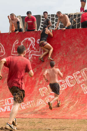 Conyers, GA, USA - August 22, 2015:  Competitors gather momentum as they run toward and climb up a wall obstacle at the Rugged Maniac Obstacle Course race in Conyers, GA.