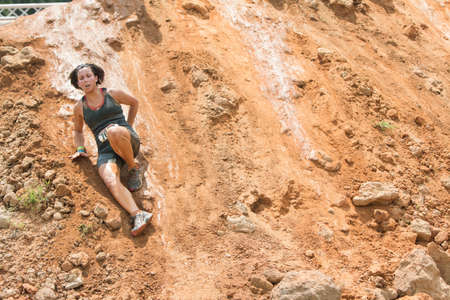struggles: Conyers, GA, USA - August 22, 2015:  A young woman struggles to make her way down a slippery dirt hill at the Rugged Maniac Obstacle Course race in Conyers, GA. Editorial