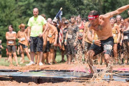 Conyers, Géorgie, États-Unis - le 22 Août, 2015: Un jeune homme tente de courir à travers les plates-formes flottantes dans une fosse d'eau boueuse au Rugged Maniac Obstacle Course course à Conyers, Géorgie. Banque d'images - 52168872
