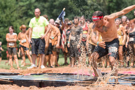 obstacle course: Conyers, GA, USA - August 22, 2015:  A young man tries to run across platforms floating in a pit of muddy water at the Rugged Maniac Obstacle Course race in Conyers, GA.