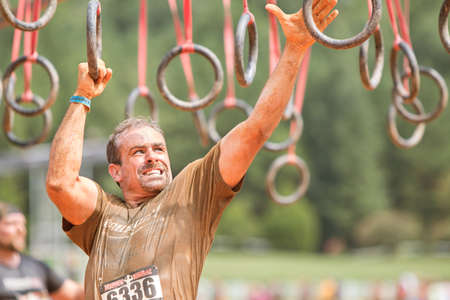 grimaces: Conyers, GA, USA - August 22, 2015:  A man grimaces as he swings from rings suspended from wood beams to keep him out of muddy water at the Rugged Maniac Obstacle Course race in Conyers, GA. Editorial