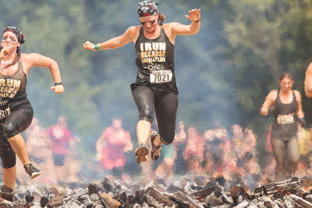 Conyers, GA, USA - August 22, 2015:  A woman hurdles over burning logs as she competes in the Rugged Maniac Obstacle Course race in Conyers, GA. Sajtókép