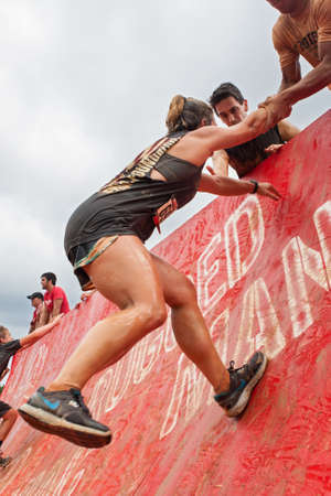 struggles: Conyers, GA, USA - August 22, 2015:  A female competitor gets an assist as she struggles to climb a wall in the Rugged Maniac Obstacle Course race in Conyers, GA.