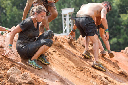 Conyers, GA, USA - August 22, 2015:  Competitors carefully make their way down a large slippery dirt mound at the Rugged Maniac Obstacle Course race in Conyers, GA. Sajtókép