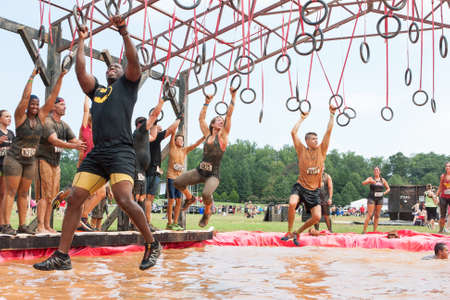 Conyers, GA, USA - August 22, 2015:  Competitors try to cross a muddy pool of water by swinging from rings at the Rugged Maniac Obstacle Course race in Conyers, GA.