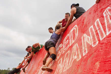 Conyers, GA, USA - August 22, 2015:  Competitors struggling to climb up a wall obstacle get a little assistance from other participants at the Rugged Maniac Obstacle Course race in Conyers, GA.