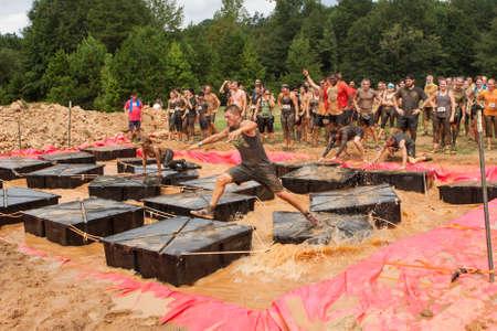 Canton, GA, USA - 17. Oktober 2015: Konkurrenten kämpfen, um ihr Gleichgewicht zu halten, während sie über schwebende plaforms in schlammigem Wasser laufen, am Obstacle Course Rennen Rugged Maniac in Conyers, GA.