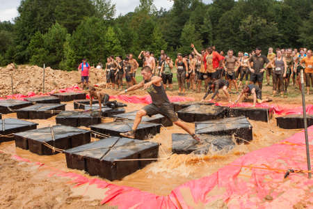Canton, GA, USA - October 17, 2015:  Competitors struggle to maintain their balance as they run across floating plaforms in muddy water, at the Rugged Maniac Obstacle Course race in Conyers, GA.