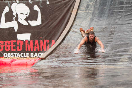 water   slide: Conyers, GA, USA - August 22, 2015:  A man goes down a giant water slide headfirst into a pool of water as he competes in the Rugged Maniac obstacle course race in Conyers, GA.