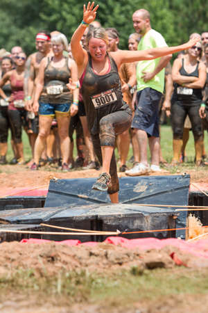Conyers, GA, USA - August 22, 2015:  A young woman tries to run across platforms floating in a pit of muddy water at the Rugged Maniac Obstacle Course race in Conyers, GA.