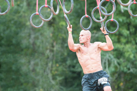 Conyers, GA, USA - August 22, 2015:  A young fit male swings from rings suspended from wood beams to keep him out of muddy water at the Rugged Maniac Obstacle Course race in Conyers, GA.