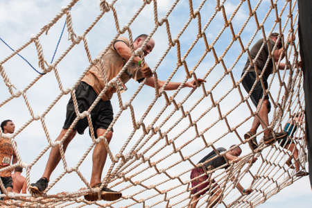 Conyers, GA, USA - August 22, 2015:  Competitors climb a cargo net on their way to the next obstacle at the Rugged Maniac Obstacle Course race in Conyers, GA.
