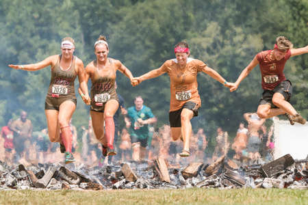 Conyers, GA, USA - August 22, 2015:  A group of women holding hands jump together over burning logs as they compete in the Rugged Maniac Obstacle Course race in Conyers, GA.