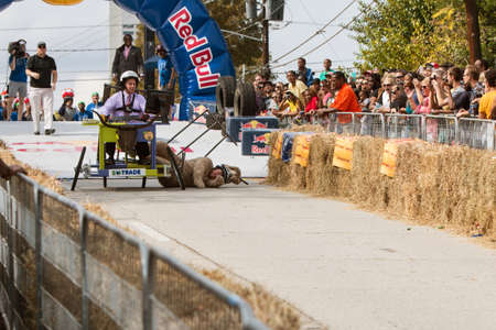 dog in costume: Atlanta, GA, USA - October 24, 2015:  A competitor wearing a furry dog costume falls from his vehicle hard onto the pavement, in the Red Bull Soap Box Derby on North Avenue in Atlanta, GA.