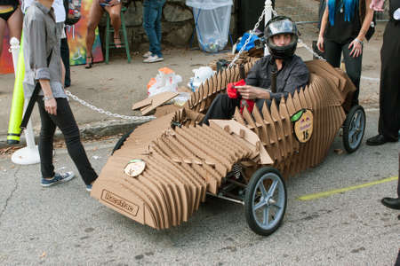 custom car: Atlanta, GA, USA - October 24, 2015:  A driver sits in his homemade vehicle made of cardboard as he waits for his run in the Red Bull Soap Box Derby on North Avenue in Atlanta, GA.