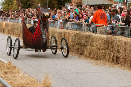 steers: Atlanta, GA, USA - October 24, 2015:  A competitor steers his teams custom made vehicle that looks like a dragon down the course at the Red Bull Soap Box Derby on North Avenue in Atlanta, GA.