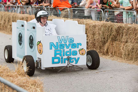 steers: Atlanta, GA, USA - October 24, 2015:  A team steers their custom made vehicle that looks like washing machines down the course at the Red Bull Soap Box Derby on North Avenue in Atlanta, GA. Editorial