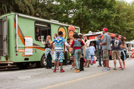 Atlanta, GA, USA - October 24, 2015:  Customers stand in line waiting to buy meals from food trucks at an event in Atlanta, GA. Editorial