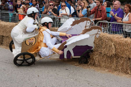 Atlanta, GA, USA - October 24, 2015:  Competitors racing a soap box derby car designed like a Roman chariot crash into hay bales at the Red Bull Soap Box Derby on North Avenue in Atlanta, GA. Editorial
