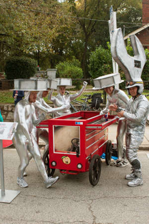 custom car: Atlanta, GA, USA - October 24, 2015:  Competitors dressed like metal bolts and a giant wrench, ham it up beside their toolbox race car before their run in the Red Bull Soap Box Derby in Atlanta, GA.