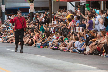 Atlanta, GA, USA - September 5, 2015:  A man dressed like a Star Trek character waves to a huge throng of spectators as he walks in the annual Dragon Con Parade down Peachtree Street in Atlanta, GA.