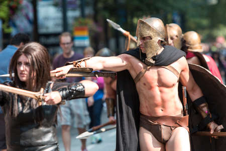 con man: Atlanta, GA, USA - September 5, 2015:  A muscular man dressed like a Spartan warrior from the movie 300, points his sword toward the crowd as he walks in the annual Dragon Con Parade in Atlanta, GA.