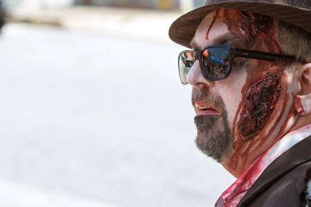 repugnant: Atlanta, GA, USA - July 25, 2015:  A man wearing elaborate zombie makeup awaits the start of the Atlanta Zombie Pub Crawl in Atlanta, GA.